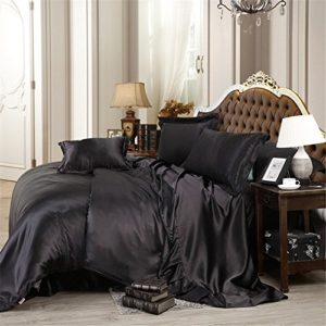 Bedroom with large bed and black sating sheets and pillows